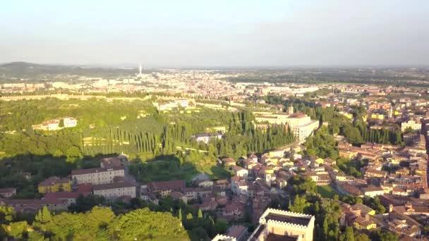 Panorama historického centra Verony, mosty přes řeku Adige. Středověké budovy s červenými střechami, Itálie. Letecké video záběry ve 4K shora na Castel San Pietro.
