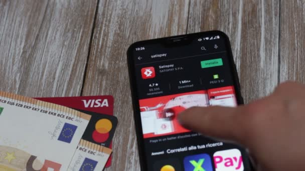 Close-up of the Satispay app in the Google Play Store on the smartphone screen. Satispay is an app for shopping in stores, sending money to friends, paying for services. In the background money and debit cards