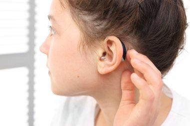 girl assumes hearing aid.