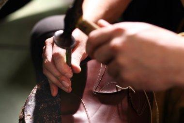 Shoemaker sews shoes