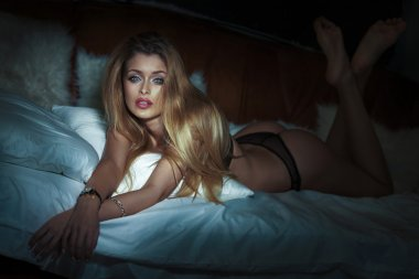 Sensual blonde woman in bed.