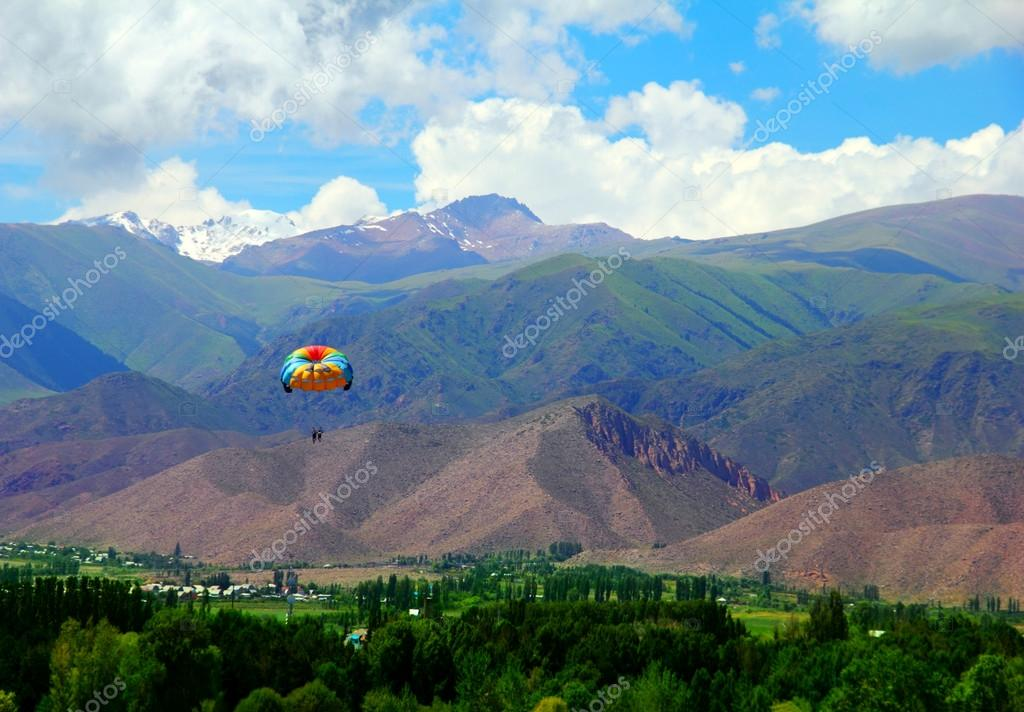 Parachute flying above green valley