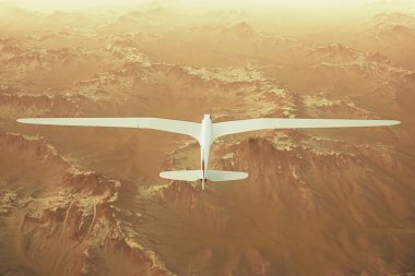 Sailplane over snow capped mountains.