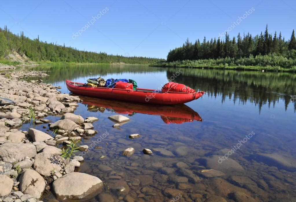 Virgin Komi forests, the red boat on the river.