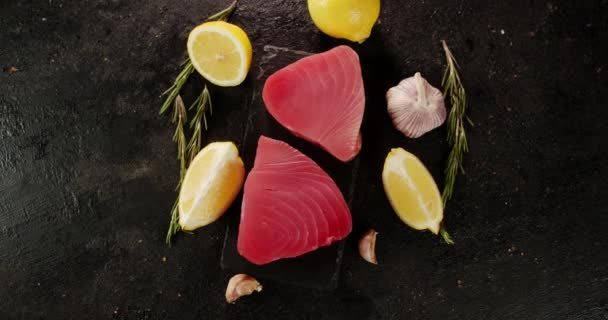 Kousky syrového tuňáka na kamenné desce s rotací citronu.