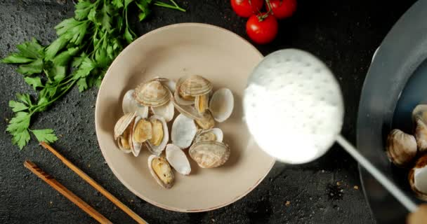 Die Venusmuscheln werden auf einen Teller aus einem Topf gelegt.