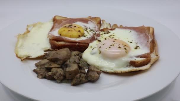 Vejce se šunkou, sýrem, chlebem a houbami na bílém otočném talíři
