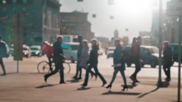 Lens blur, out of focus. A crowd of people is walking along the pedestrian crossing against the background of passing cars. People are walking around the big city. Slow motion.