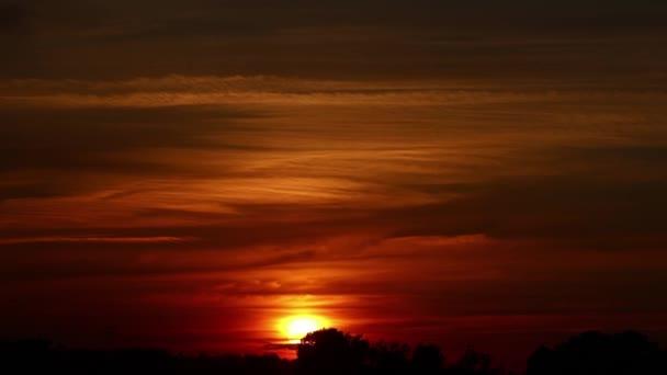 A naplemente színei a felhős égbolton. A nap megérinti a horizontot. Mélyvörös-narancssárga színátmenet