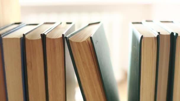 Muž dává knihy na své místo v knihovně zblízka. Vnitřní pohled na polici