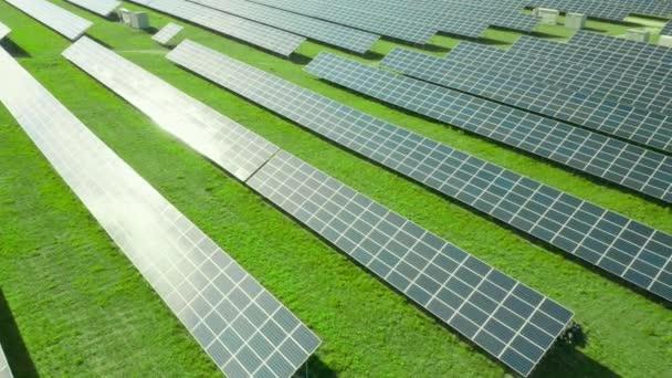 Repülés a napelem mentén a zöld mezőn. Naperőmű zöld energia előállításához. Az ég tükröződése a napelemben