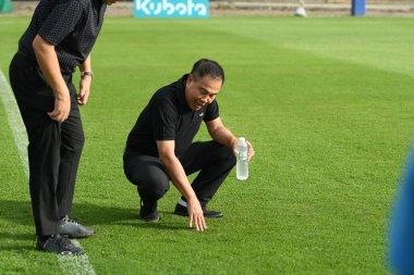Bangkok, Thailand - May 30, 2019::Police General Somyot Poompanmuang President of FA Thailand checking grass during training before king cup 2019 tournament at alpine football camp, Thailand