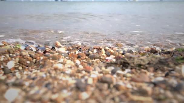 Zblízka vln lapování na oblázkové pláži