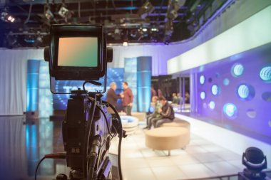Television studio with camera and lights - recording TV show. Shallow depth of field - focus on camera stock vector