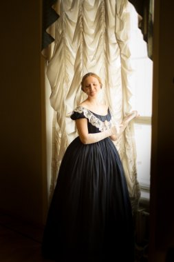 Young woman in long ball dress standing at the window at the ball