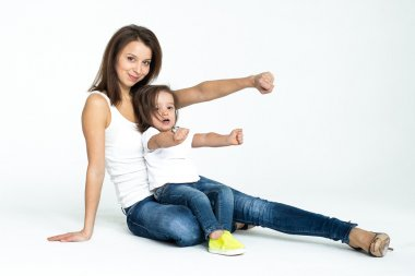 Little girl in white T-shirt and jeans playing with mom