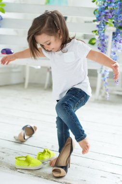 Little girl in white T-shirt and jeans playing and trying on her mother's high heels