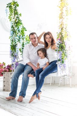 Young loving family: mother, father and daughter in a bright interior