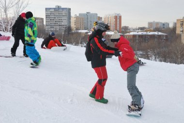 Young snowboarder and instructor during the descent from the mountain ski resort