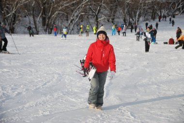 The young girl in a red jacket snowboarder goes down the slope at a ski resort in Moscow
