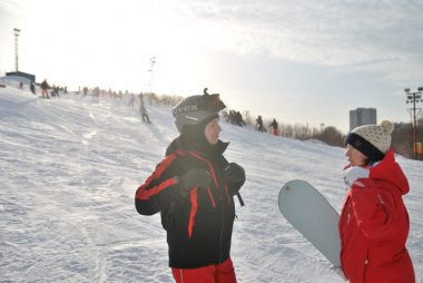 Young snowboarder and instructor during the descent from the mountain ski resort in Moscow