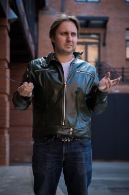 Young man in sunglasses and a leather jacket standing on stone stairs