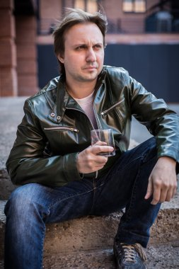 The young man in a leather jacket with a glass of whiskey