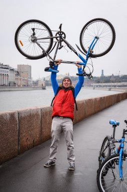 A young man picks up a bicycle over his head during a trip to the city in the fall after the rain