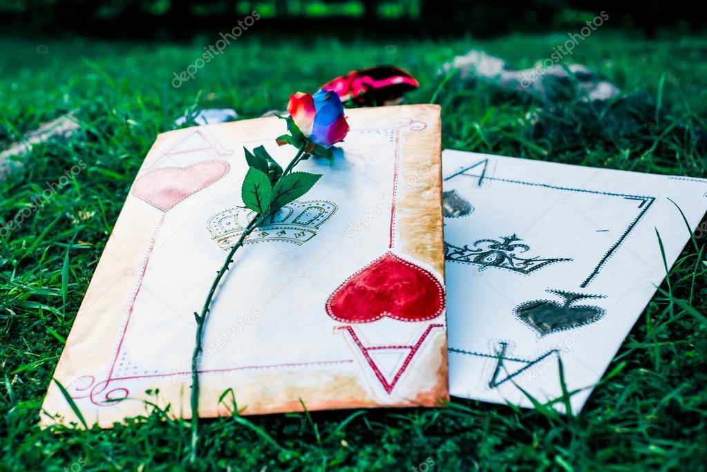 Huge playing cards and a rose - the scenery for a fairy tale about Alice
