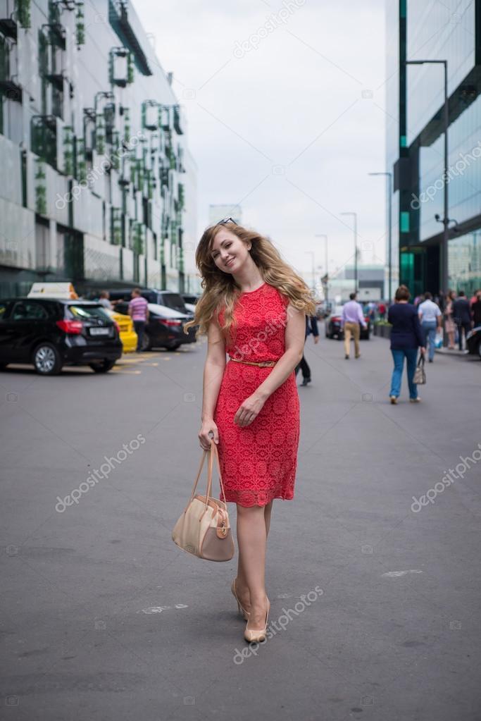 13f2816b4b2 Chica en vestido coral paseos con un bolso de mano entre los rascacielos  del centro de negocios– imagen de stock