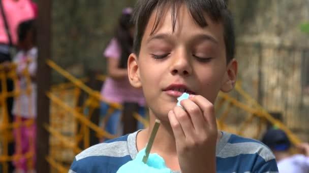 Giovane ragazzo che mangia al campo da giuoco