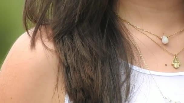 Žena nosí šperky náhrdelníky a přívěsky