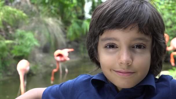 Frühreifer hispanischer Junge lächelt im Zoo
