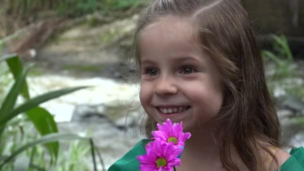 glücklicheres Mädchen mit Blumen am Fluss