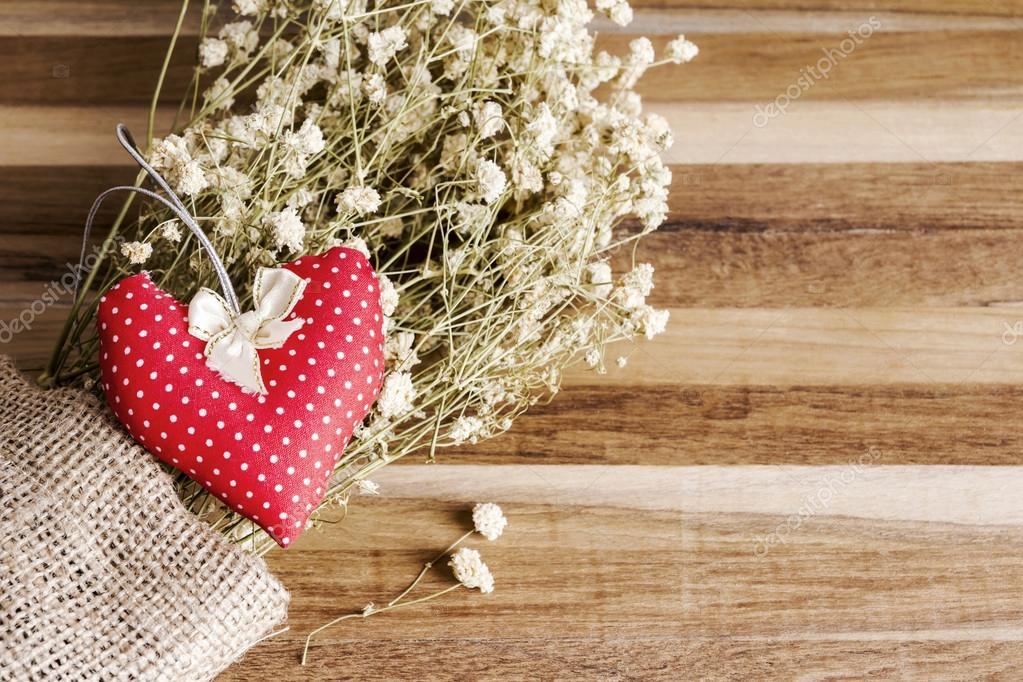 Herz-Gewebe und trockenen Blumen auf hölzernen Hintergrund ...