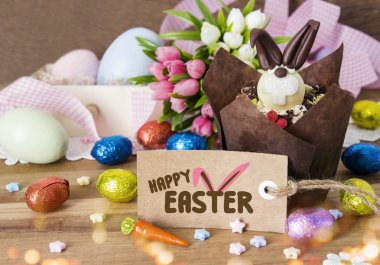 Happy Easter decoration of cupcake and chocolate eggs on wooden background