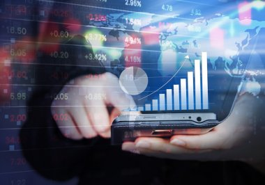 Business woman are checking stock market graph by using mobile p