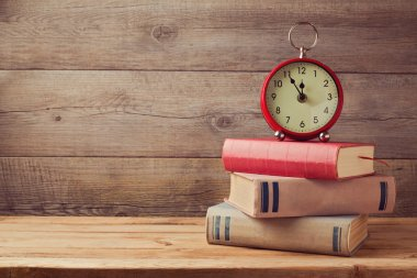 Books and clock on wooden table