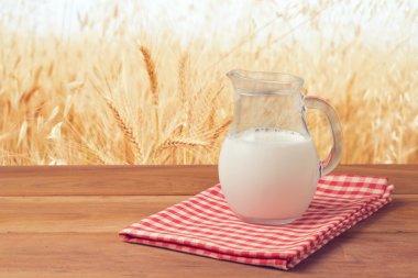 Milk jug over wheat field