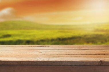 Wooden table over blur landscape