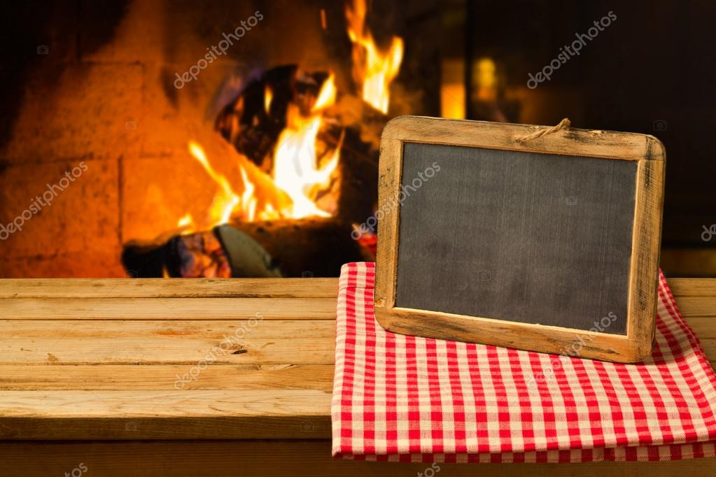 Chalkboard on wooden table over fireplace