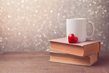 cup and heart on books