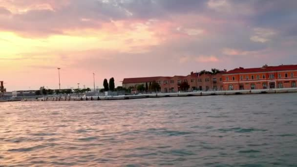 Benátský trajektový terminál při západu slunce z pohybující se lodi, Benátky, Itálie. Stabilizovaný výstřel, který odhalí více západu slunce.