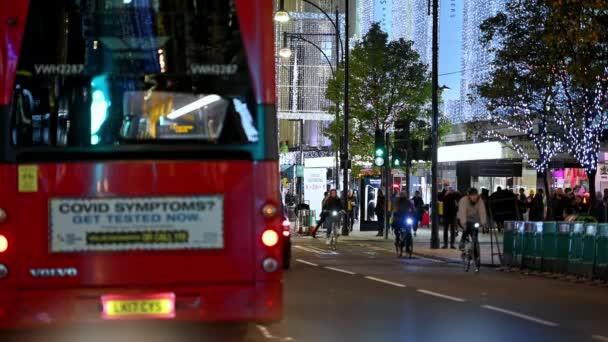 LONDÝN - 3. listopadu 2020: Red London Double Decker Bus s výstražnou značkou Covid odjíždějící z autobusové zastávky na Oxford Street osvětlené vánočními světly