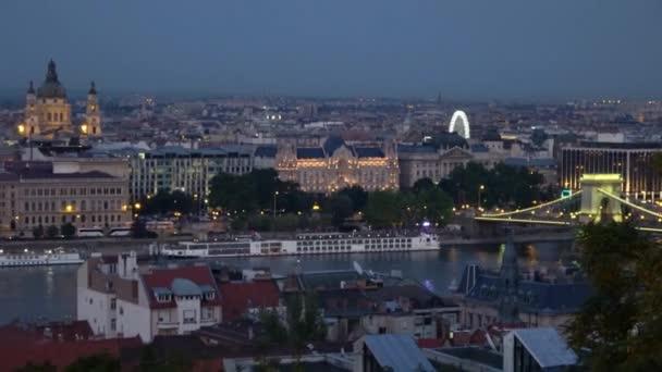 Zoom and Pan from The Budapest Eye to The Margaret Bridge in Budapest, Hungary pass A Magyar Parlament épülete látványos fényben tündökölt késő este.