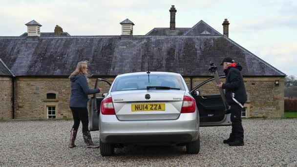 Richmond, North Yorkshire, UK - April 02, 2021: Man and young woman fit front roof rack bar to a silver car