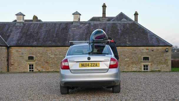 Richmond, North Yorkshire, UK - April 02, 2021: A man loads a slalom kayak onto roof rack bars on a silver car and tightens the loading straps