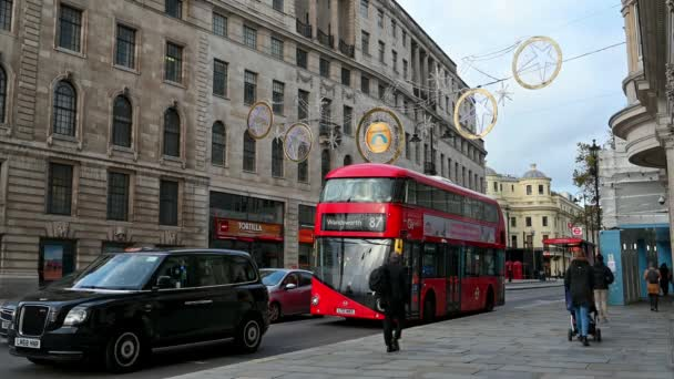 LONDON - NOVEMBER 3, 2020: Christmas decoration lights above Red London Double Decker bus and black London Taxi cab on The Strand, London