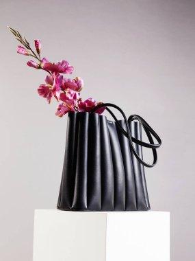 Flowers in stylish leather Handbag, fashion still life. Female Black Bag