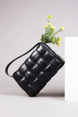 Stylish Leather Handbag with yellow Flowers, fashion still life. Female Black Bag